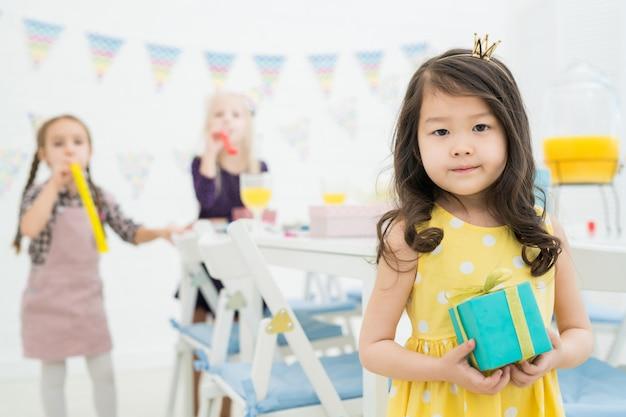 Aantrekkelijke aziatische kleine koningin met geschenkdoos