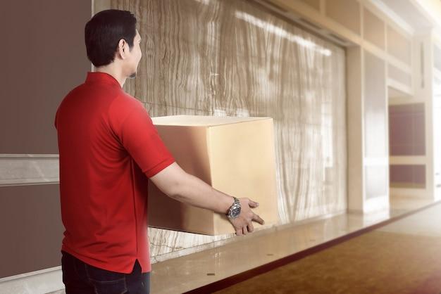 Aantrekkelijke aziatische leveringsmens die het pakket houdt