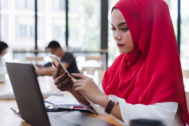 Aantrekkelijke aziatische moslim accountant rode hijab met behulp van telefoon en financiële rapporten in co-working.