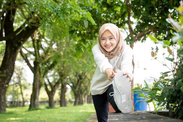 Aantrekkelijke aziatische moslimvrouw die haar been alleen tijdens buitensport uitrekt