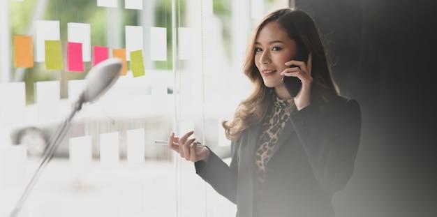 Aantrekkelijke aziatische onderneemster die op de telefoon met haar klant spreekt
