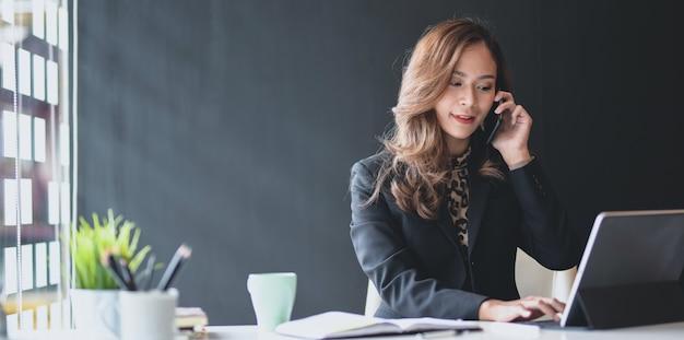 Aantrekkelijke aziatische onderneemster die op de telefoon met klant spreekt