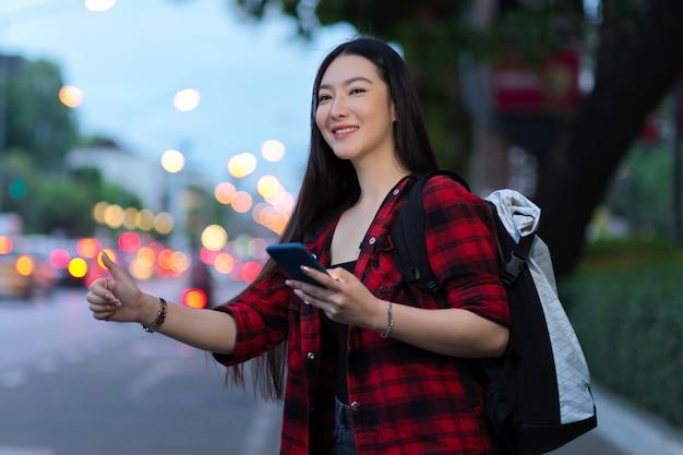 Aantrekkelijke aziatische solo-reiziger die lokaal taxivervoer belt met smartphone en rugzak
