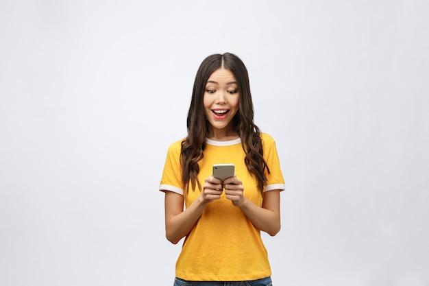 Aantrekkelijke aziatische tiener die haar gsm-scherm met vrolijk gezicht bekijkt