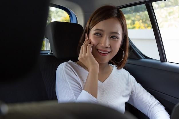 Aantrekkelijke aziatische vrouw die aan de telefoon praat tijdens het reizen en op de achterbank van de auto zit