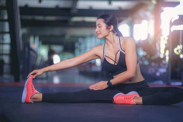 Aantrekkelijke aziatische vrouw die haar spieren uitrekt voordat ze gaat trainen in de sportschool