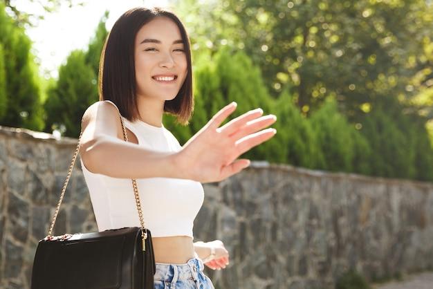 Aantrekkelijke aziatische vrouw die in park loopt en eindegebaar toont