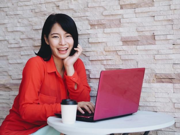 Aantrekkelijke aziatische vrouw die laptop in koffiewinkel met behulp van.