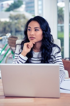 Aantrekkelijke aziatische vrouw die laptop met hand op kin in bureau met behulp van
