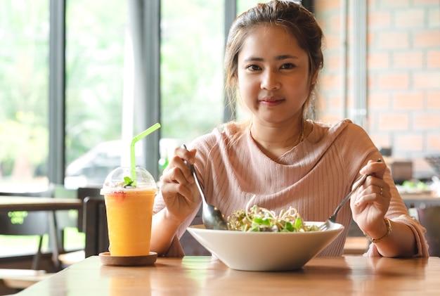 Aantrekkelijke aziatische vrouw die plantaardige salade met jus d'orange eten smoothie bij lunch in koffie