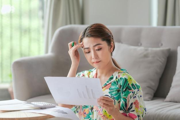 Aantrekkelijke aziatische vrouw die thuis huiswerk doet