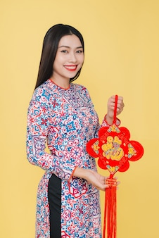 Aantrekkelijke aziatische vrouw die traditioneel kostuum draagt, dat op gele achtergrond wordt geïsoleerd. tekst betekent geluk.