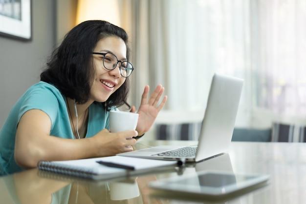 Aantrekkelijke aziatische vrouw die video met laptop computer telefoneert en hand golft. jonge vrouw in blauw shirt praten met familie en mensen via internettechnologie thuis. online e-learning en studeren