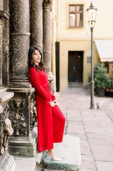 Aantrekkelijke aziatische vrouw in het lange rode kleding stellen die zich dichtbij de oude de bouwkolom bevinden in oude stad