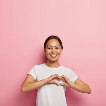 Aantrekkelijke aziatische vrouw maakt hartvorm gebaar, drukt liefde uit, zegt wees mijn valentijn, lacht positief, draagt witte outfit, vormt tegen roze muur met lege ruimte. lichaamstaal concept