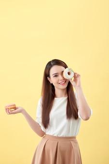 Aantrekkelijke aziatische vrouw met twee donuts met schattige lachende uitdrukking op gele achtergrond