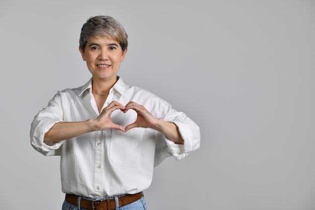 Aantrekkelijke aziatische vrouw van middelbare leeftijd die lacht in liefde met hartsymbool en vorm met handen geïsoleerd op een witte achtergrond