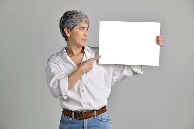 Aantrekkelijke aziatische vrouw van middelbare leeftijd die leeg uithangbord toont dat op witte achtergrond wordt geïsoleerd