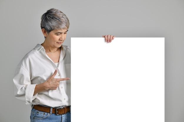 Aantrekkelijke aziatische vrouw van middelbare leeftijd die met de vingers wijst naar een leeg bord dat op een witte achtergrond wordt geïsoleerd