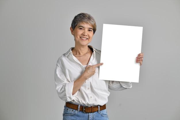 Aantrekkelijke aziatische vrouw van middelbare leeftijd tonen en wijzend op leeg bord geïsoleerd op een witte achtergrond. naar de camera kijken