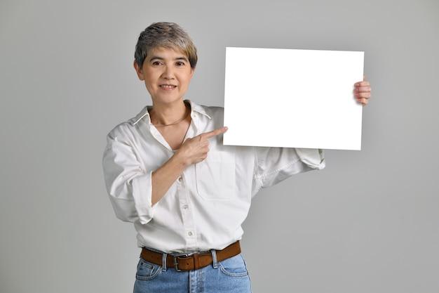 Aantrekkelijke aziatische vrouw van middelbare leeftijd weergegeven: leeg bord geïsoleerd op een witte achtergrond. naar de camera kijken