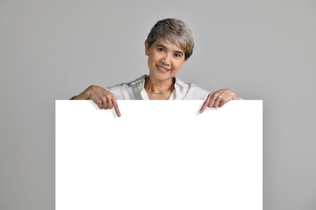 Aantrekkelijke aziatische vrouw van middelbare leeftijd wijzende vingers op leeg bord geïsoleerd op een witte achtergrond. naar de camera kijken