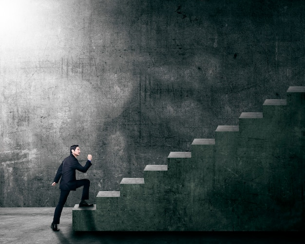 Aantrekkelijke aziatische zakenman die een trap opvoert