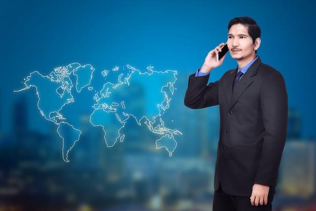 Aantrekkelijke aziatische zakenman die op mobiele telefoon spreekt