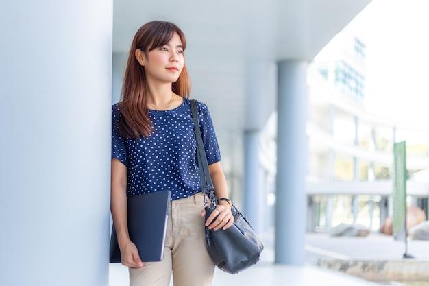 Aantrekkelijke aziatische zakenvrouw die tegen het gebouw leunt en haar computer en portemonnee vasthoudt