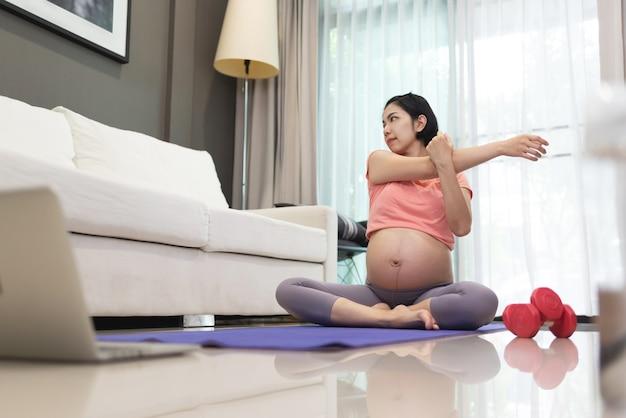 Aantrekkelijke aziatische zwangere vrouw in roze sportkleding die wapens thuis uitrekt.