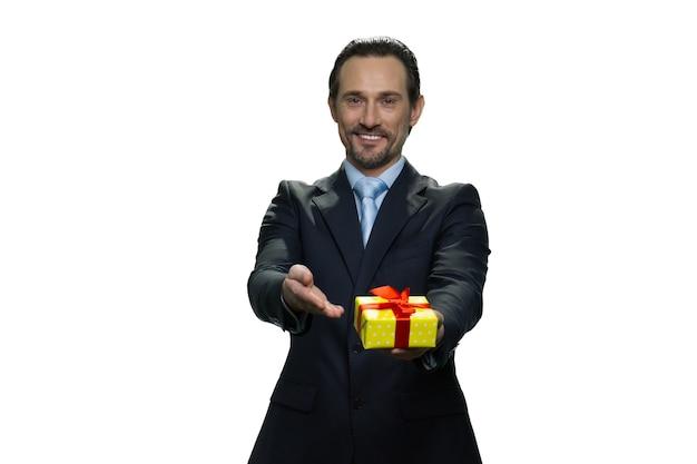 Aantrekkelijke baas die een cadeautje overhandigt. gelukkig volwassen man in pak geïsoleerd op een witte muur.