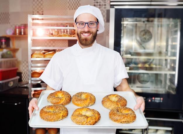Aantrekkelijke baker in wit uniform met een dienblad met vers gebakken bagels met sesam en maanzaad op het oppervlak van een broodfabriek of bakkerij