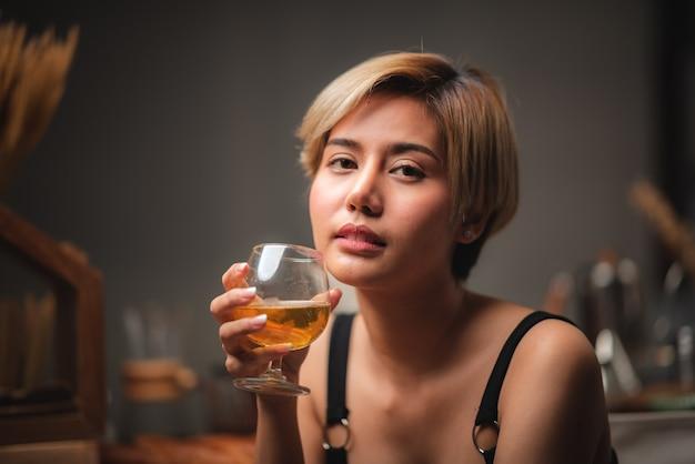 Aantrekkelijke barman meisje houdt in haar handen verse cocktail aan de toog voor viering