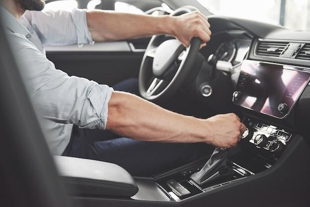 Aantrekkelijke bebaarde gelukkig man in goede auto.