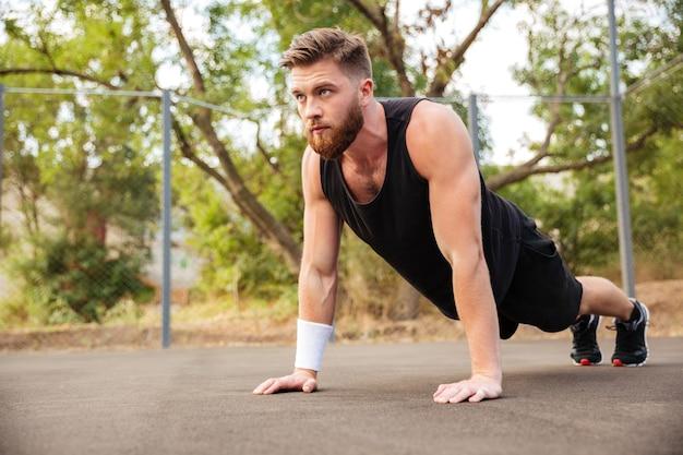 Aantrekkelijke bebaarde jonge sportman doet push-ups buitenshuis