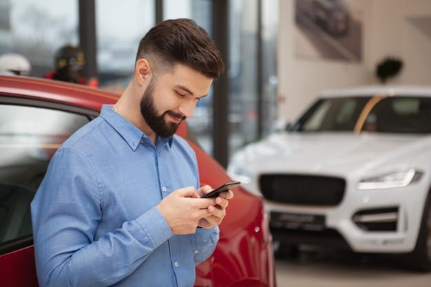 Aantrekkelijke bebaarde man die lacht tijdens het gebruik van zijn slimme telefoon bij autodealer, kopie ruimte