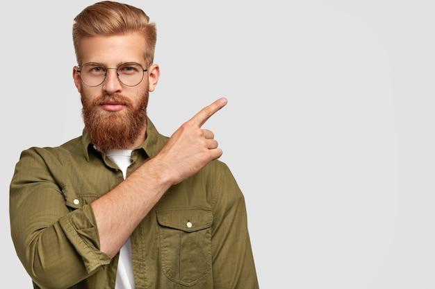 Aantrekkelijke bebaarde man met dikke roodbruine baard en haar, aantrekkelijk uiterlijk, wijst naar de rechterbovenhoek