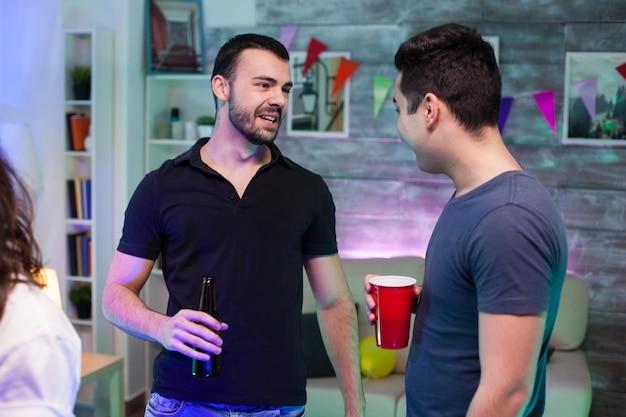 Aantrekkelijke bebaarde man met een biertje op een feestje en praten met zijn vriend.