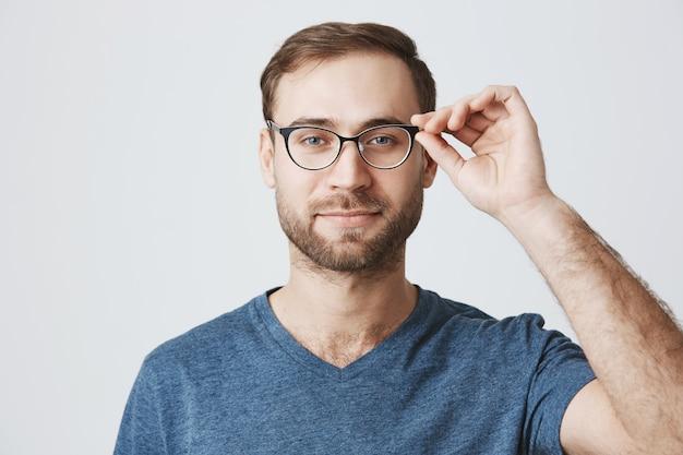 Aantrekkelijke bebaarde man plukken bril bij opticien winkel