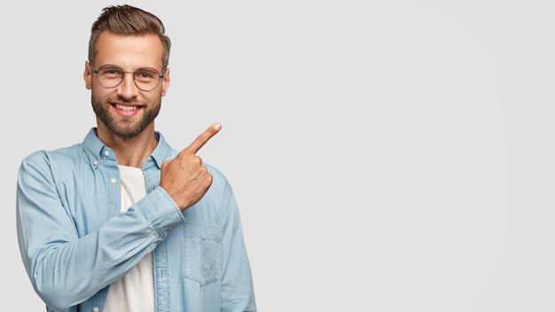Aantrekkelijke bebaarde man poseren tegen de witte muur