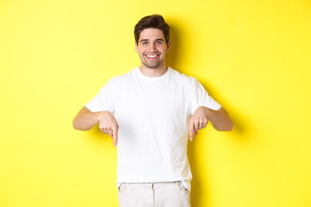 Aantrekkelijke bebaarde man wijzende vingers naar beneden, evenement banner tonen, staande over gele muur