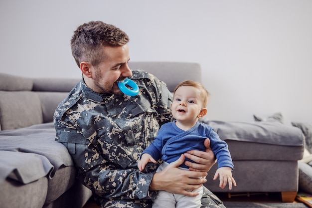 Aantrekkelijke bebaarde soldaat zittend op de vloer in de woonkamer, houdt zijn geliefde schattige babyjongen, bijtring in zijn mond en plaagt hem.