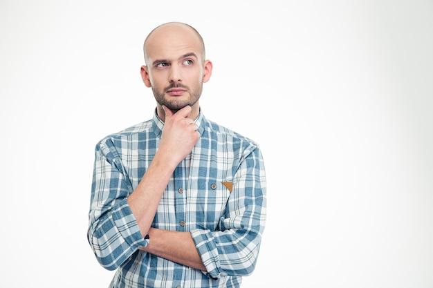 Aantrekkelijke bedachtzame jonge man in geruit hemd die wegkijkt over de witte muur