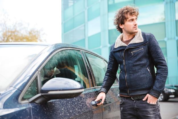 Aantrekkelijke bedachtzame knappe, zelfverzekerde, gekrulde jongeman in een zwarte jas die in de buurt van de auto staat en gaat rijden