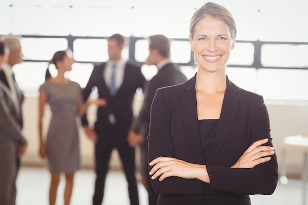 Aantrekkelijke bedrijfsvrouw die bij camera glimlacht