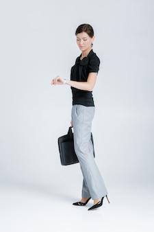 Aantrekkelijke bedrijfsvrouw die een omslag met documenten houdt en horloge bekijkt