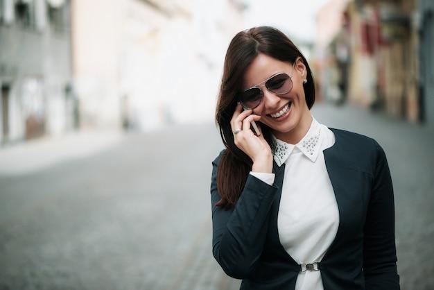 Aantrekkelijke bedrijfsvrouw die en op mobiele telefoon in een stadsstraat loopt spreekt.
