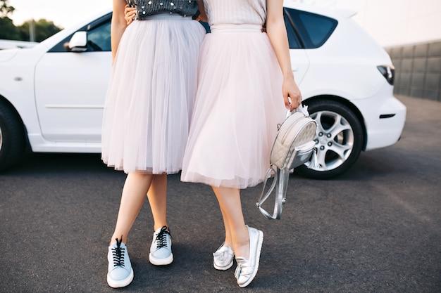 Aantrekkelijke benen van fotomodellen in tule rokken en sneakers op witte auto.