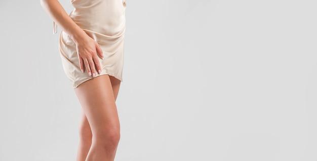 Aantrekkelijke benen van vrouw in nachtjapon zijde. sierlijke vrouwelijke figuur in lingerie.