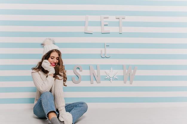 Aantrekkelijke, bescheiden dame in witte gebreide outfit kijkt verlegen naar beneden en raakt haar mooie gezicht aan. portret met nieuwjaarsbelettering op gestreepte muur